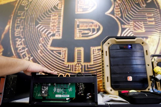 FILE PHOTO: A cryptocurrency mining computer is seen in front of bitcoin logo during the annual Computex computer exhibition in Taipei, Taiwan June 5, 2018. REUTERS/Tyrone Siu/File Photo