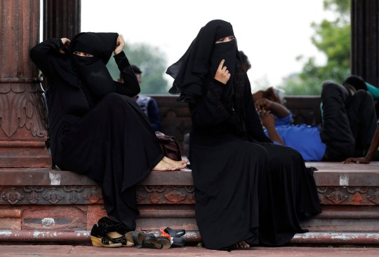 """FILE - In this Aug. 22, 2017 file photo, Indian Muslim women rest inside Jama Masjid mosque in New Delhi, India. India's government on Wednesday, Sept. 19, 2018, approved an ordinance to implement a top court ruling striking down the Muslim practice that allows men to instantly divorce. The government decision came after it failed to get approval of Parliament a year after the court ruled that the practice of triple """"talaq"""" violated the constitutional rights of Muslim women. (AP Photo/Tsering Topgyal, File)"""