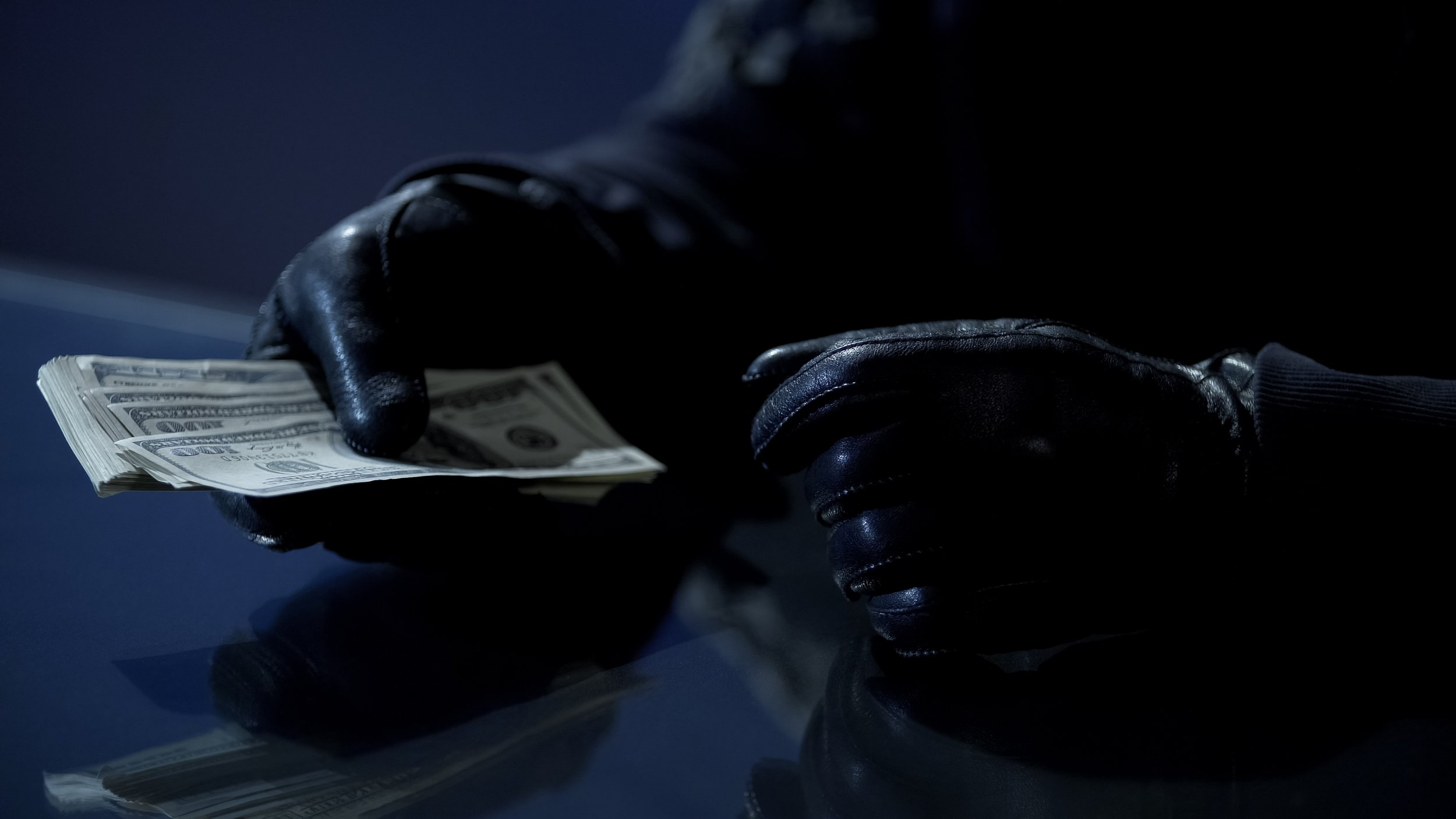 Criminal counting ransom money for kidnapping, blackmail, contract killing; Shutterstock ID 1038183205; Purchase Order: -