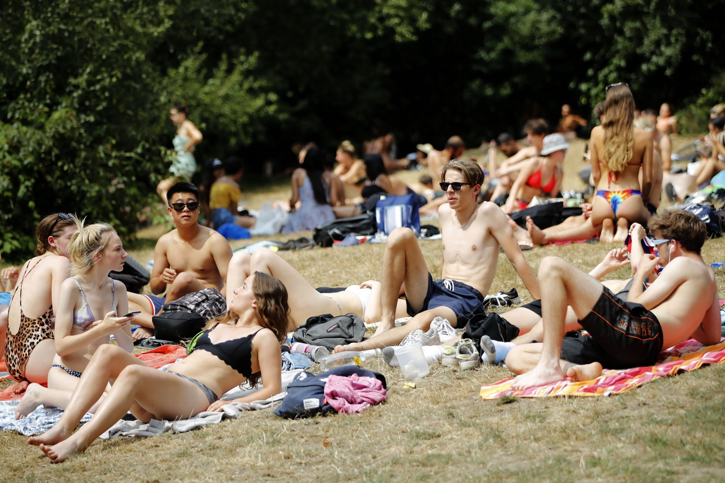 Sunbathers relax on Hampstead Heath in London on July 26, 2018. - Britain has been in the grip of its longest heatwave in decades, sparking wildfires in northwest England, water restrictions in Northern Ireland and record-breaking temperatures in Scotland. (Photo by Tolga AKMEN / AFP) (Photo credit should read TOLGA AKMEN/AFP/Getty Images)