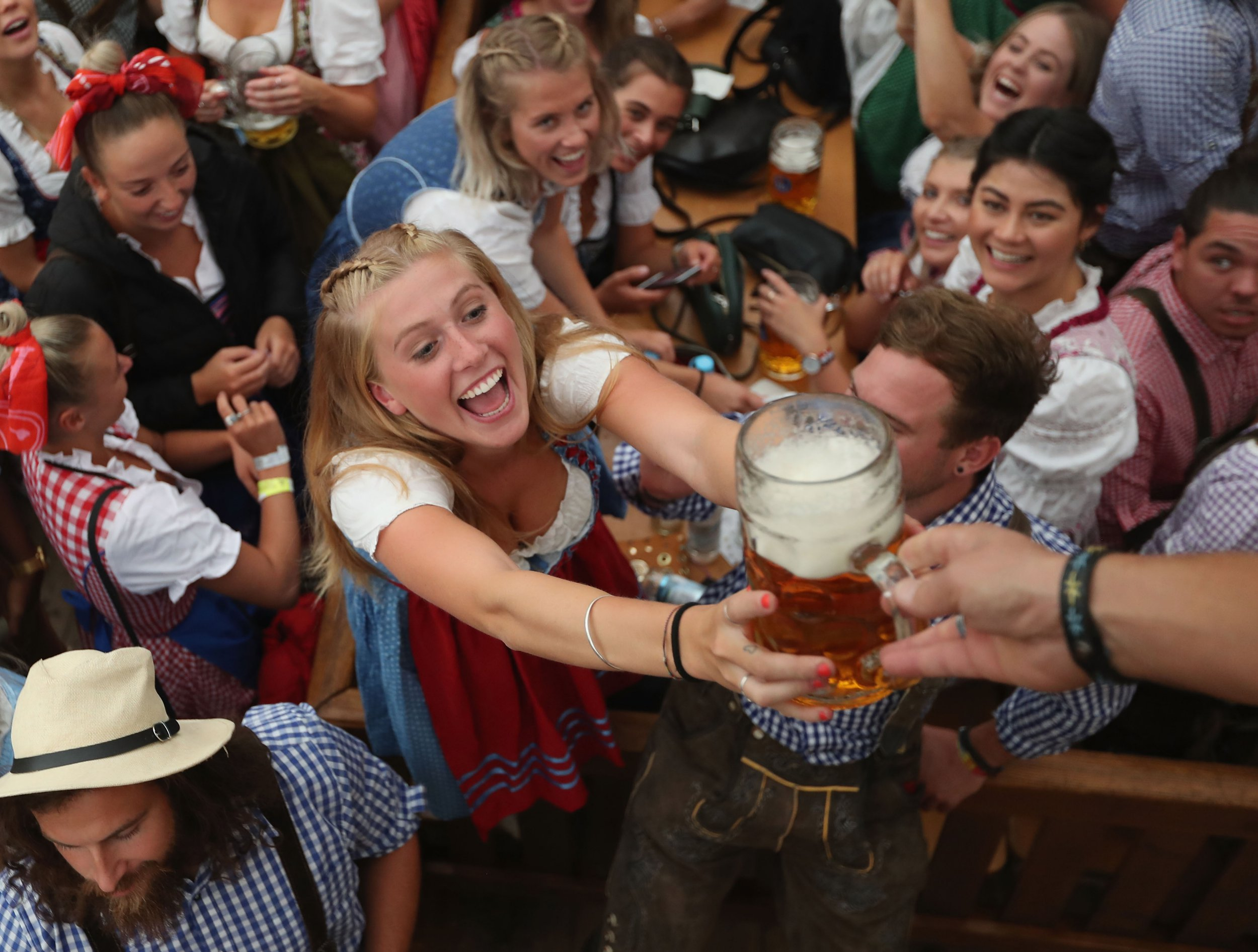 MUNICH, GERMANY - SEPTEMBER 22: Visitors celebrate in a beer tent at the opening day of the 2018 Oktoberfest beer festival on September 22, 2018 in Munich, Germany. The Oktoberfest lasts until October 7 and is the world's largest beer festival. The beer festival typically draws over six million visitors. (Photo by Alexandra Beier/Getty Images)