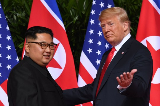 TOPSHOT - US President Donald Trump (R) gestures as he meets with North Korea's leader Kim Jong Un (L) at the start of their historic US-North Korea summit, at the Capella Hotel on Sentosa island in Singapore on June 12, 2018. - Donald Trump and Kim Jong Un have become on June 12 the first sitting US and North Korean leaders to meet, shake hands and negotiate to end a decades-old nuclear stand-off. (Photo by SAUL LOEB / AFP) (Photo credit should read SAUL LOEB/AFP/Getty Images)