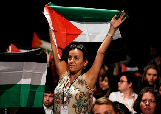 LIVERPOOL, ENGLAND - SEPTEMBER 25: Delegates wave Palestinian flags during a speech about the situation in Palestine on day three of the Labour Party Conference on September 25, 2018 in Liverpool, England. The four-day annual Labour Party Conference takes place at the Arena and Convention Centre in Liverpool and is expected to attract thousands of delegates and features keynote speeches from party politicians and over 450 fringe events. (Photo by Ian Forsyth/Getty Images)