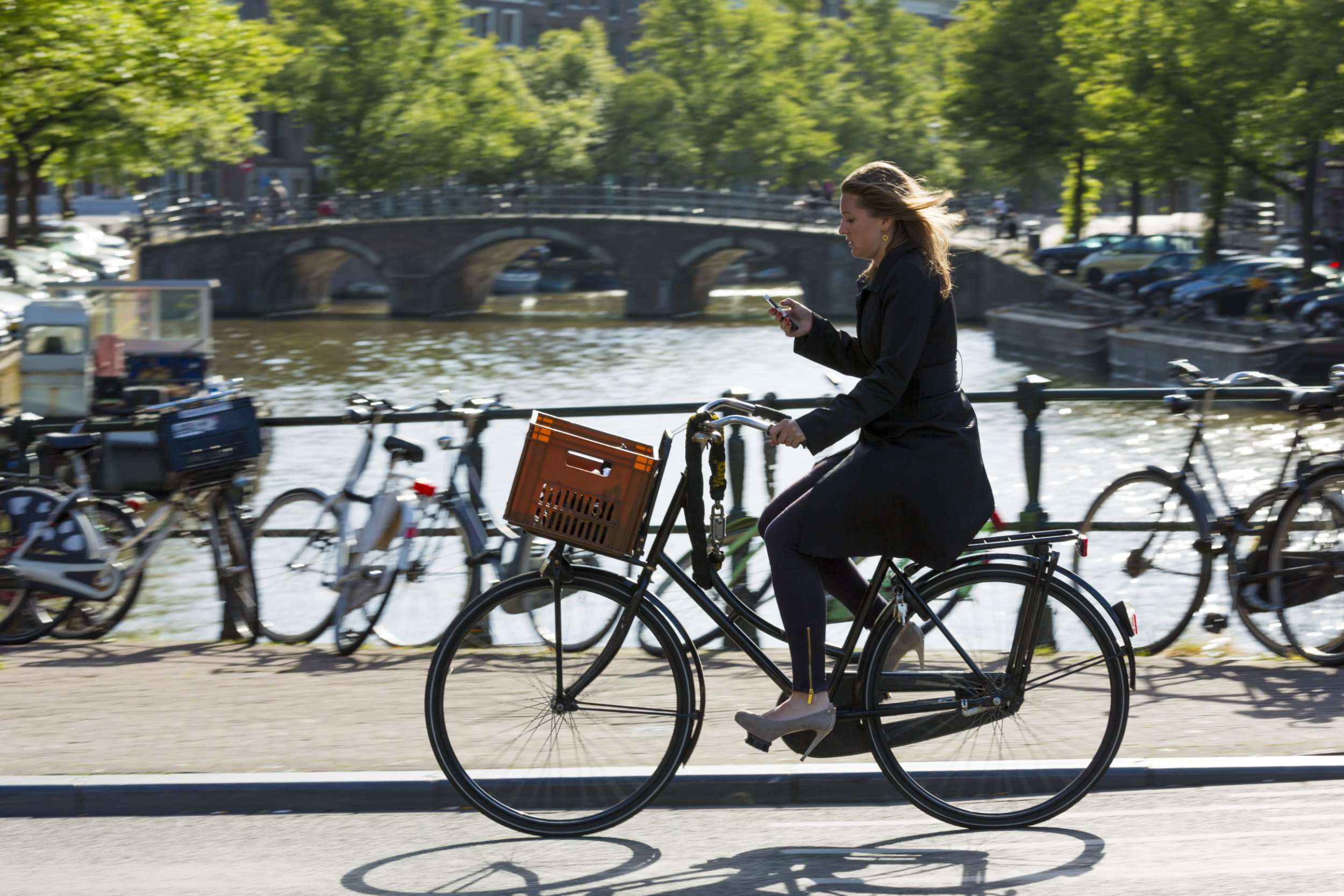 Young woman wearing high heels shoes, carrying iPhone cycling out for the evening across bridge in Amsterdam, Holland. (Photo by Tim Graham/Getty Images)