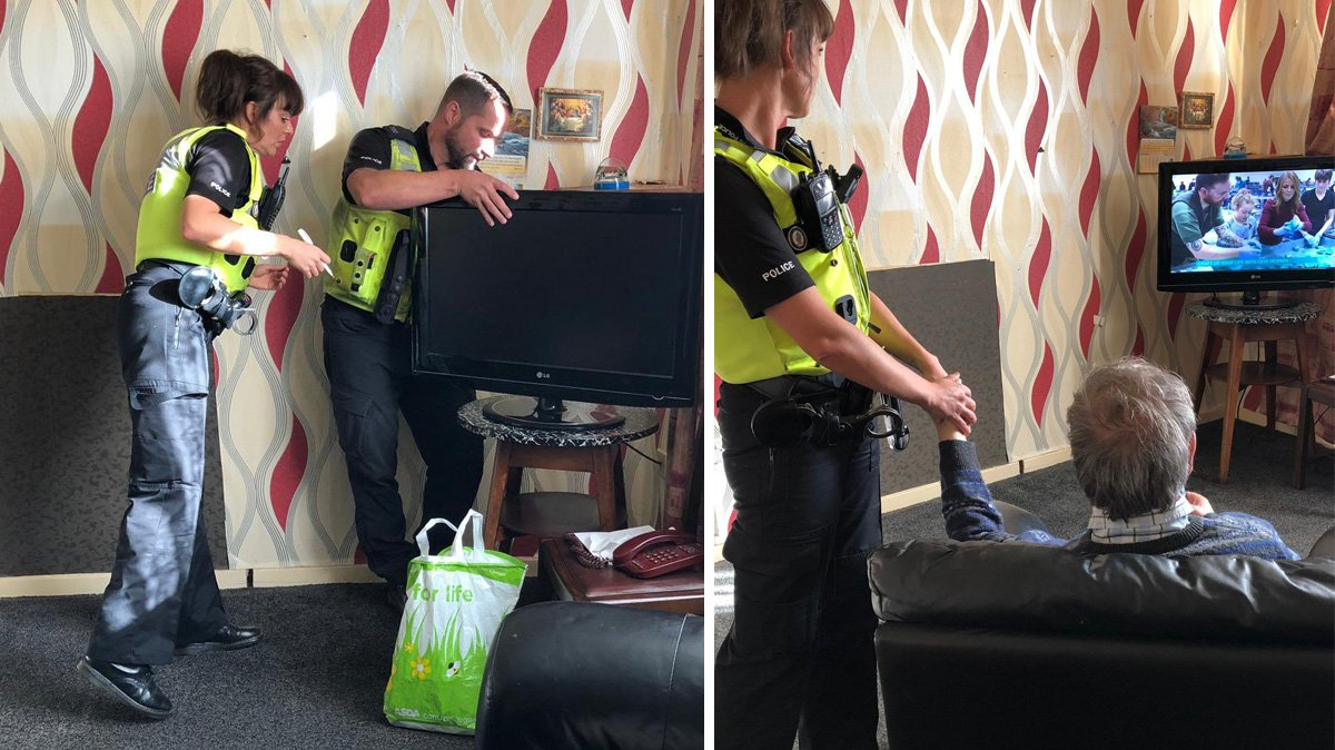 Poignant moment police officer holds elderly man's hand after his wife died