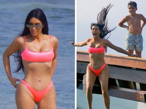 Kim Kardashian risks losing her diamond earrings again as she leaps into the sea