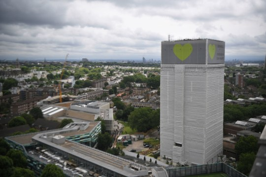 A banner with a green heart is wrapped around the Grenfell Tower one year on since the blaze, which claimed 72 lives.