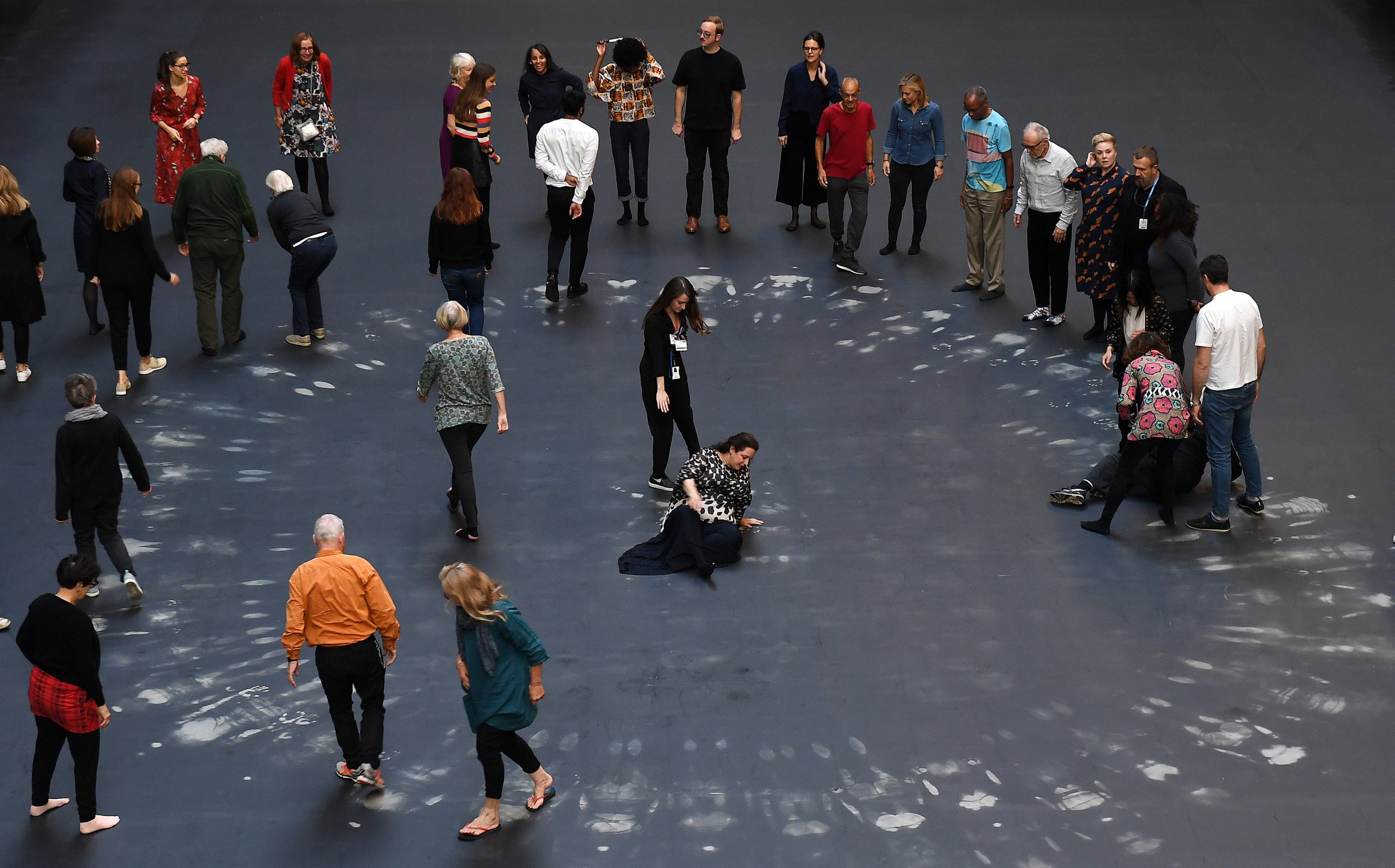 epa07061103 Cuban artist and activist Tania Bruguera (C) stands with volunteers on her installation during its unveiling in the Turbine Hall at Tate Modern in London, Britain, 01 October 2018. The art project created in response to the global migration crisis as part of the annual Hyundai Commission will be on show from 02 October 2018 to 24 February 2019. The installation 'invites visitors to take part in symbolic actions by revealing a hidden image beneath a heat-sensitive floor'. EPA/ANDY RAIN