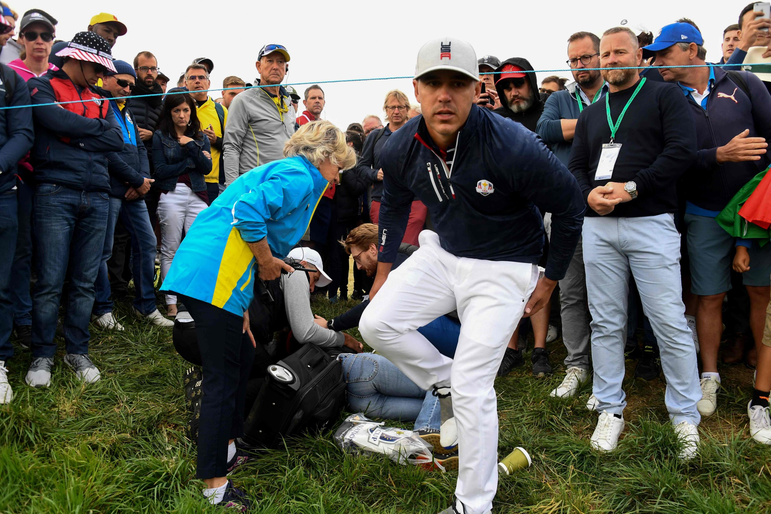 TOPSHOT - US golfer Brooks Koepka (R) reacts next to an injured spectator who fell during the fourball match on the first day of the 42nd Ryder Cup at Le Golf National Course at Saint-Quentin-en-Yvelines, south-west of Paris on September 28, 2018. (Photo by FRANCK FIFE / AFP)FRANCK FIFE/AFP/Getty Images