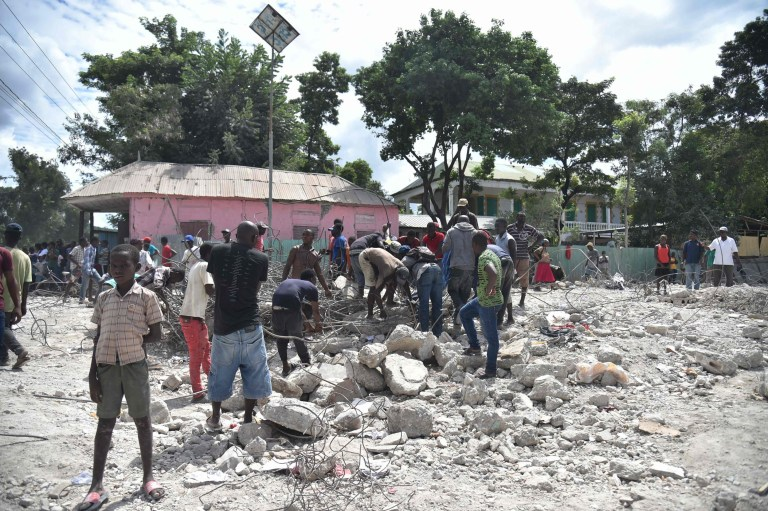 Haitian people collect metal on October 7, 2018 in Gros Morne, Haiti, from the destroyed auditorium, after the earthquake that struck north of Haiti, on October 6, 2018. - A body was rescued after a 5.9-magnitude earthquake struck off the northwest coast of Haiti late Saturday, killing at least 11 people, injuring more than 130 others and damaging homes in the Caribbean nation, authorities said. The epicenter of the quake was located about 19 kilometers (12 miles) northwest of the city of Port-de-Paix, the US Geological Survey reported. (Photo by HECTOR RETAMAL / AFP)HECTOR RETAMAL/AFP/Getty Images