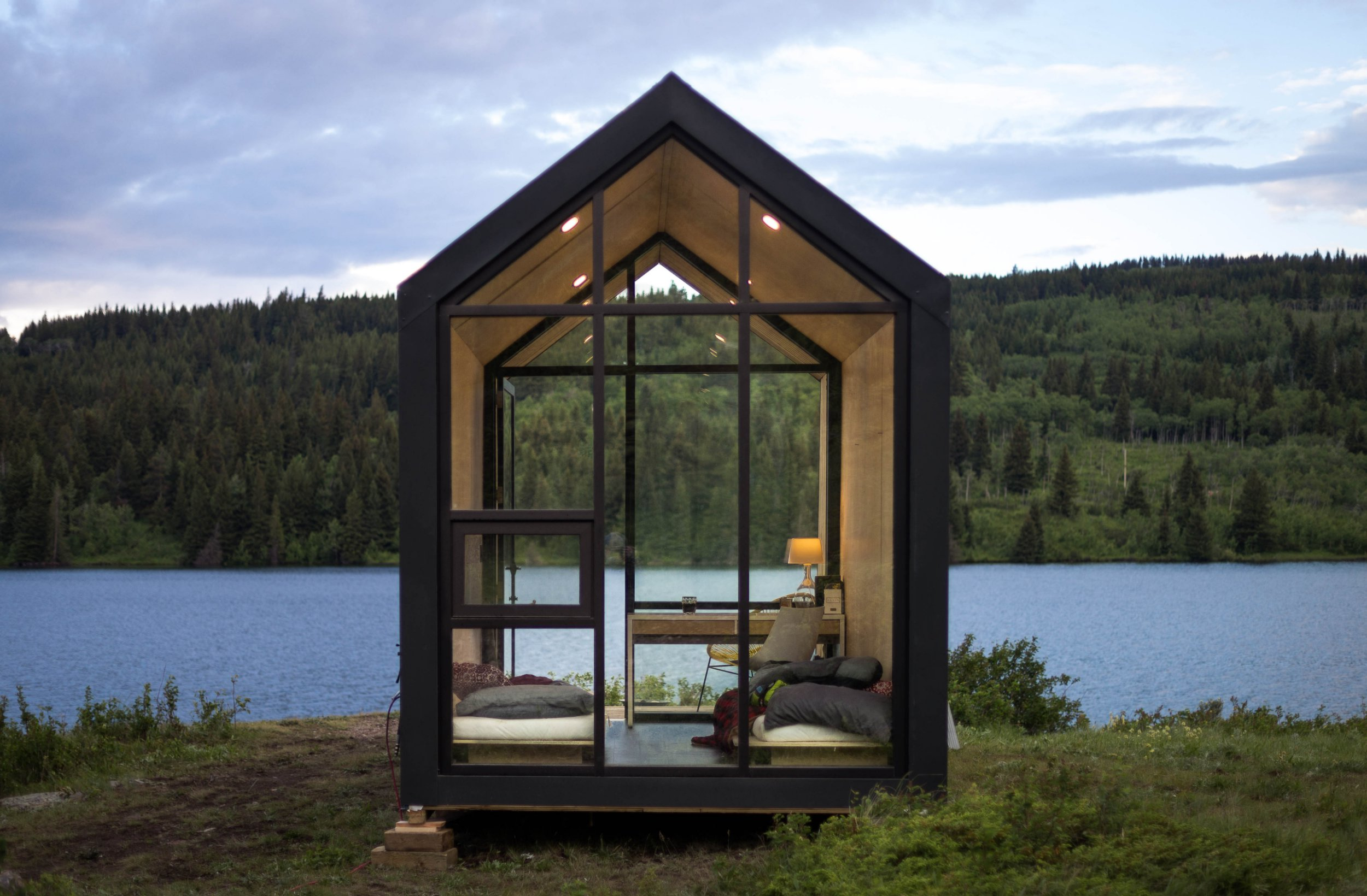 THIS STUNNING ??19k tiny house could be perfect for living off the grid as you can drop it almost anywhere without a permit. Incredible images show the 106-square-foot property in the wilderness with its huge windows allowing perfect views of the surrounding countryside. Other striking shots show the tiny structure illuminated at night, its basic but comfortable interiors and people enjoying a fire on comfortable chairs just outside the house. Aiming to take the guesswork out of the process, DROP Structures has designed a prefab house, called Mono, that can be placed almost anywhere in North America for less than ??19k. Ryan Abernathy / mediadrumimages.com