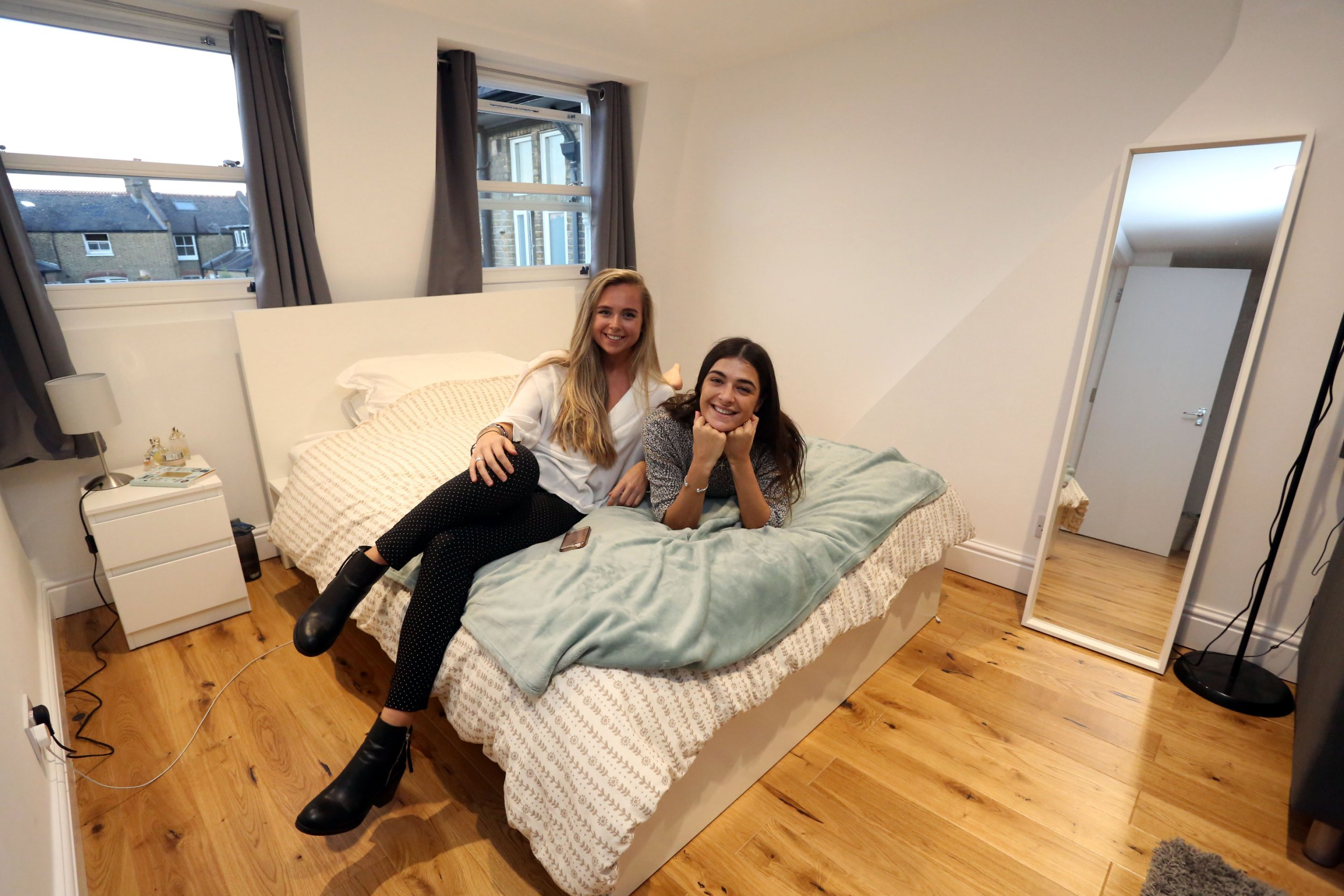 WHAT I RENT: CLAPHAM LONDON, OCTOBER 9TH 2018. Renters Jennifer White, 26, (right) and Celine Brown, 24, (left) are pictured in Jennifer's bedroom at their rented flat in Clapham, London, 8th October 2018. The three bedroom flat in Clapham is rented individually by the bedroom, Celine pays ?813, Jennifer pays ?835 and their third housemate pays ?760 a month. Photo credit: Susannah Ireland
