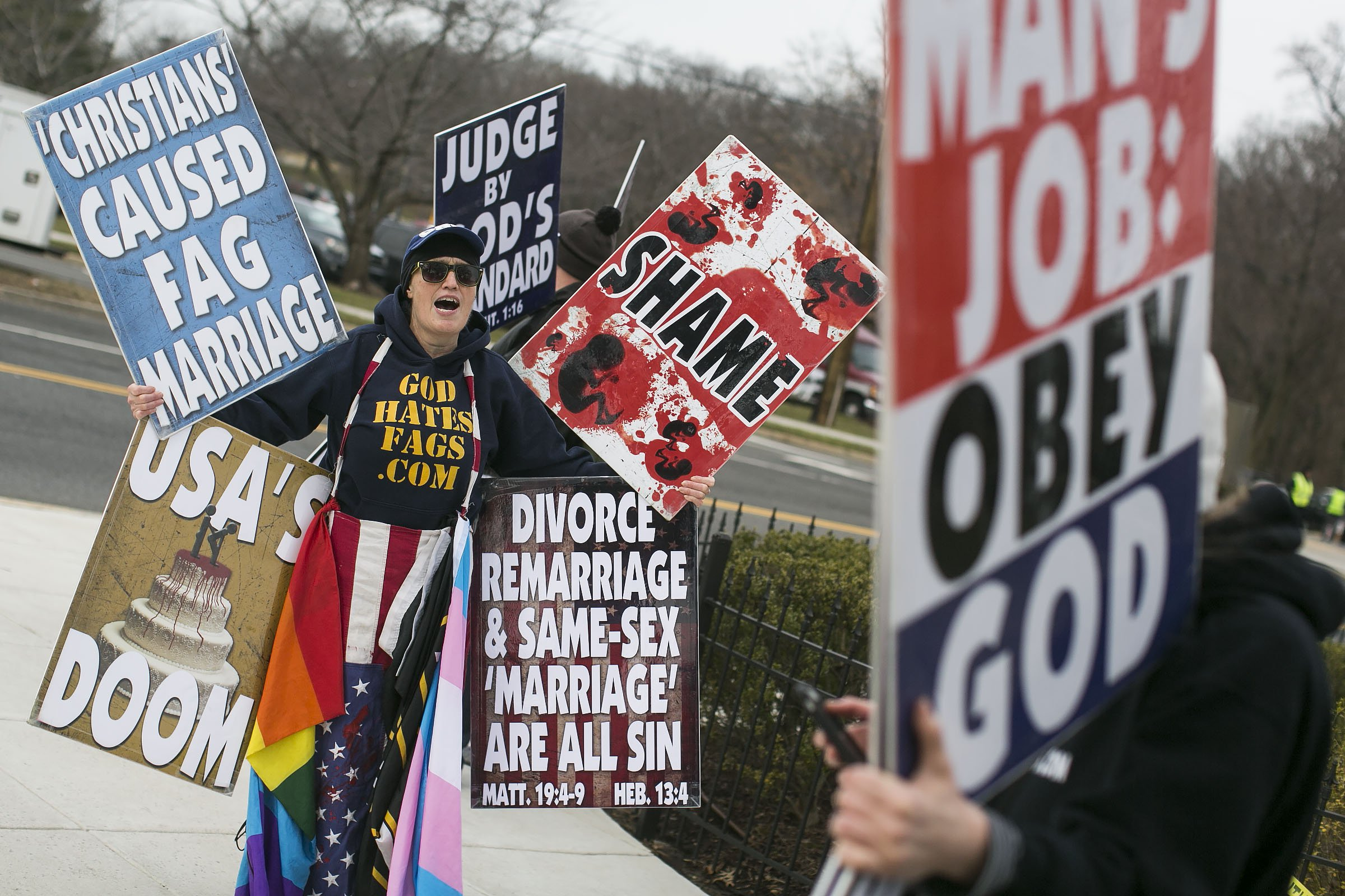 UNITED STATES - FEB. 20 - Members of the Westboro Baptist Church, based out of Topeka, Kansas, picket before the casket containing the body of the late Supreme Court Associate Justice Antonin Scalia arrives at the Basilica of the National Shrine of the Immaculate Conception in Washington for funeral mass services, Saturday, Feb. 20, 2016. (Photo By Al Drago/CQ Roll Call)