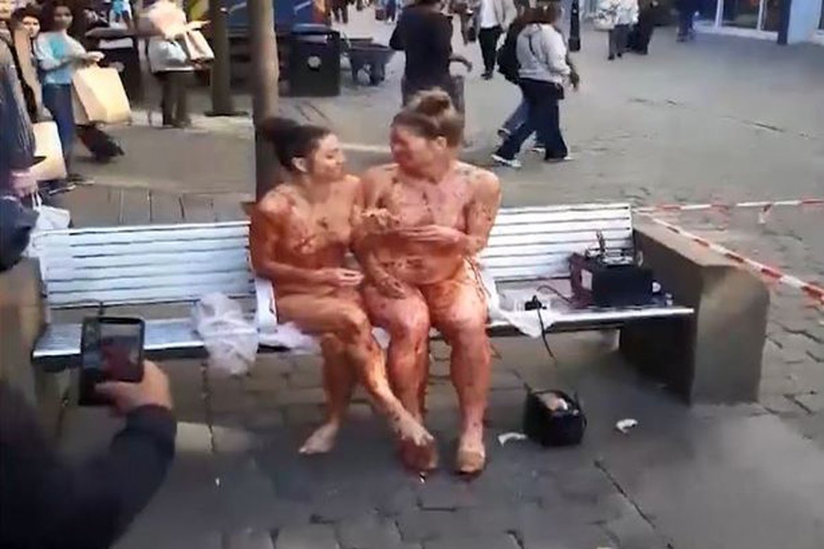 This is the moment two naked women apparently covered in jam sat on a bench in the middle of a city centre . Bewildered shoppers stopped to watch the spectacle as it unfolded on Market Street, in Manchester, just before midday on Wednesday (October 10). A crowd formed around the two women, who sat on a bench outside Barclays bank in the middle of the busy shopping street.