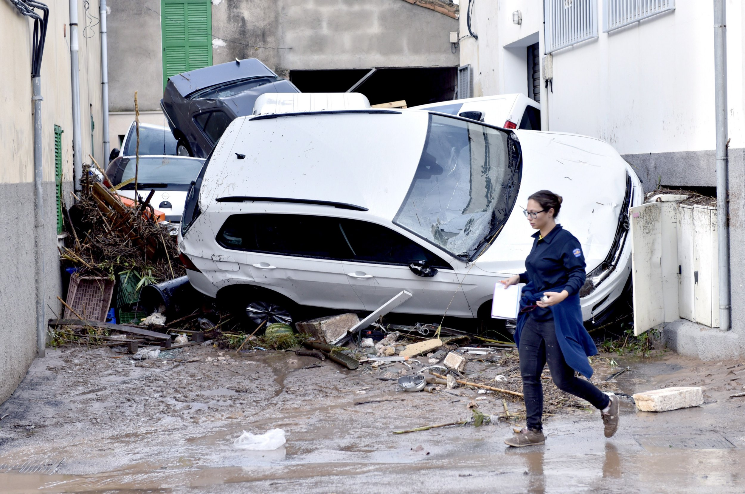epa07083711 A resident walks past a pile of vehicles after they were damaged by flash floods in the village of Sant Llorenc des Cardasar in Mallorca, Spain, 10 October 2018. At least ten people died and a 5-years-old boy is missing due to heavy rains which caused the torrent of Sant Llorenc to overflow. Some 300 members of emergency services are taking part in the search operation. EPA/ATIENZA