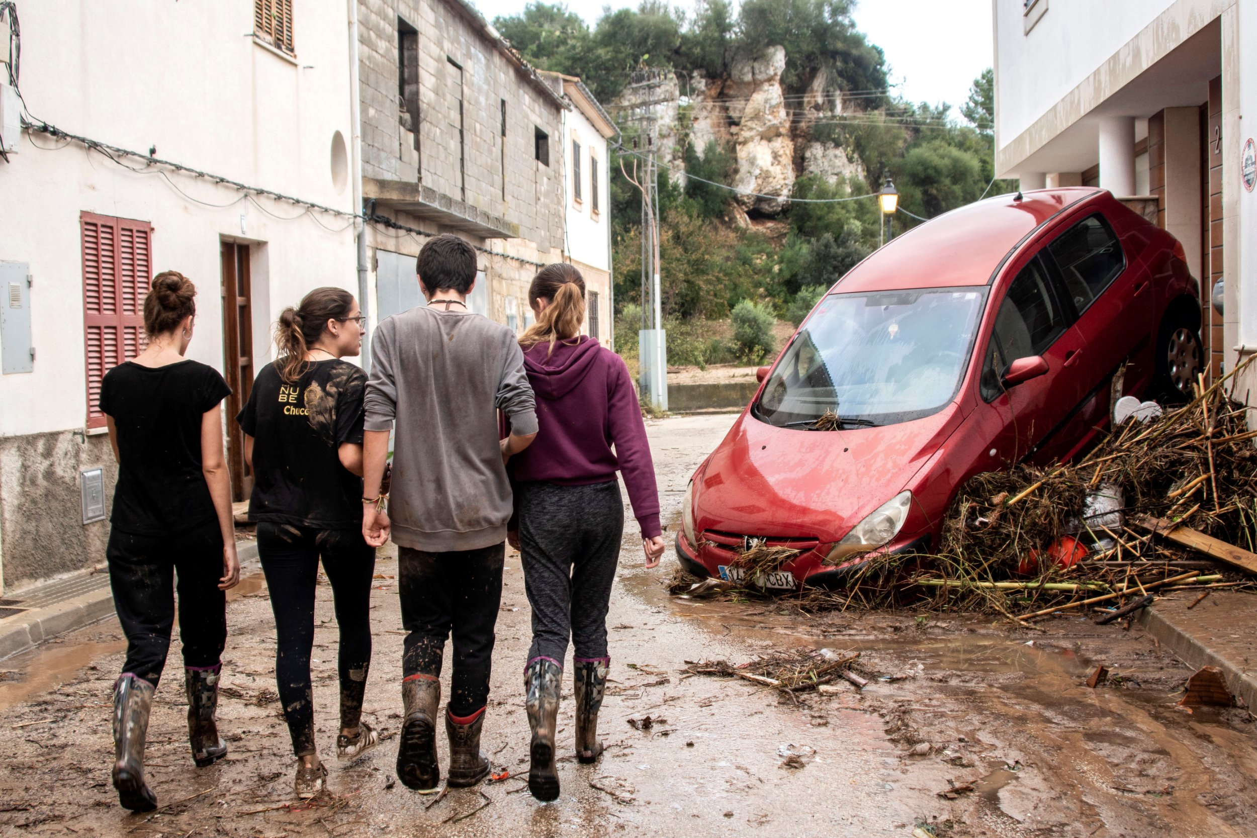 epa07083931 Residents walk along a muddy street during clean-up efforts after flash floods hit the village of Sant Llorenc des Cardasar in Mallorca, Spain, 10 October 2018. At least ten people died and a 5-years-old boy is missing due to heavy rains which caused the torrent of Sant Llorenc to overflow. Some 300 members of emergency services are taking part in the search operation. EPA/CATI CLADERA