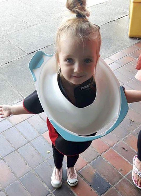 PIC FROM Caters News - (PICTURED: Darcy-lillian Hillberg, 4, from Penarth, South Wales, with the toilet seat around her neck) - This is the hilarious moment a four year old managed to get her head stuck in a TOILET SEAT taking firefighters 45 minutes to remove.Mischievous Darcy-lillian Hillberg managed to get her entire head lodged in the seat and couldnt get it off. Mum, Gemma, 32, used all her strength to try and free her daughters head, as well as handfuls of washing up liquid, Vaseline and body creams.SEE CATERS COPY