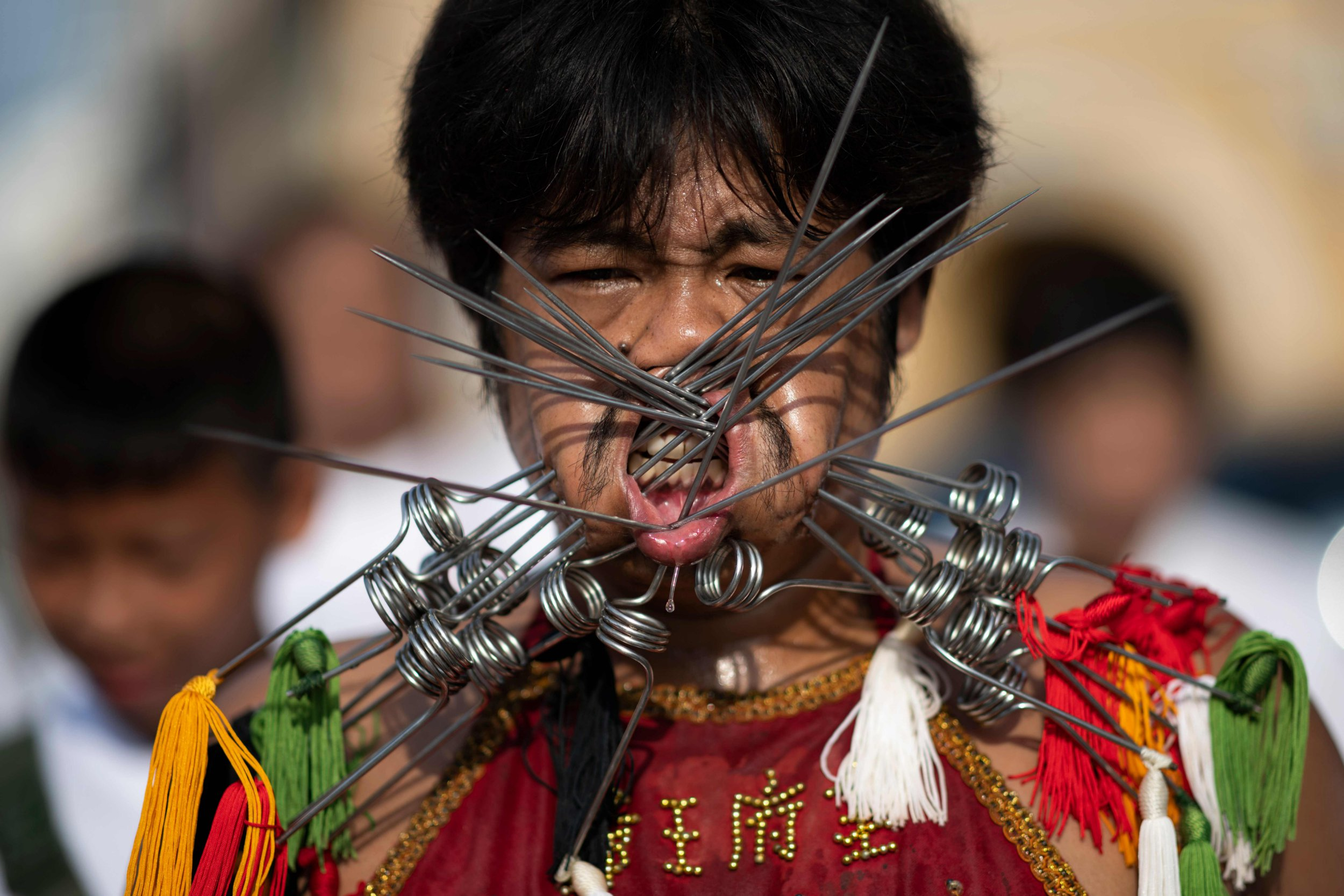 A devotee of the Loem Hu Thai Su shrine parades with multiple skewers pierced through his cheeks during the annual Vegetarian Festival in Phuket on October 12, 2018. - The festival begins on the first evening of the ninth lunar month and lasts for nine days, with many religious devotees slashing themselves with swords, piercing their cheeks with sharp objects and committing other painful acts to purify themselves, taking on the sins of the community. (Photo by Jewel SAMAD / AFP)JEWEL SAMAD/AFP/Getty Images