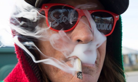 Bill Semeniuk, 67, smokes cannabis in Kamloops, British Columbia, Wednesday, Oct. 17, 2018. Canada became the largest country with a legal national marijuana marketplace as sales began early Wednesday. (Jonathan Hayward/The Canadian Press via AP)