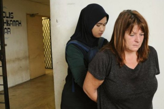 John Jones' wife Samantha seen as her hands held behind her back by a Malaysian law officer / A British man stabbed to death on Malaysian holiday island of Langkawi after rowing with his wife who has been arrested on suspicion of murder. John William Jones, 62, was found on the floor of his house with a stab wound to the chest at 2.30am this morning / Source: MOL