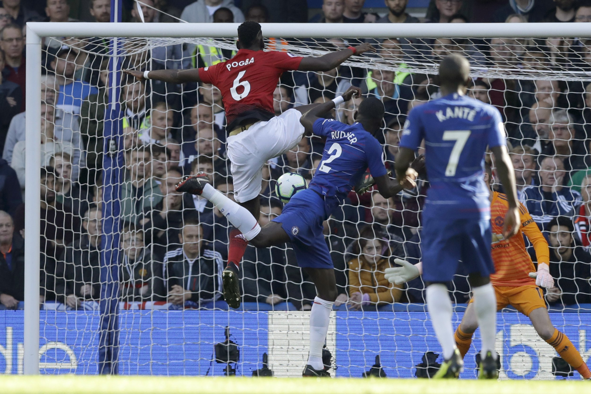 Chelsea's Antonio Ruediger, center, head the ball next to ManU midfielder Paul Pogba, left, to score his side's first goal during their English Premier League soccer match between Chelsea and Manchester United at Stamford Bridge stadium in London Saturday, Oct. 20, 2018. (AP Photo/Matt Dunham)