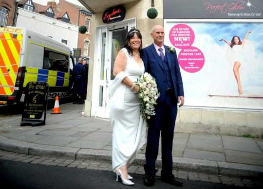 This is the unexpected moment a newlywed couple posed for a wedding photo - as a massive police raid took place behind them, uncovering nearly 1,000 CANNABIS plants. See SWNS story SWBRweed. When Sarah and Alan Buckley planned their wedding in Gloucester city centre, they certainly did not dozens of police officers and hundreds of cannabis plants to be part of their wedding shoot. But the happy couple went along with it, and beamed for photos in front of a huge building in Northgate Street, where windows had been flung open and heat lamps could be seen inside. The new Mr and Mrs Buckley posed for the photo with a police van just behind them as the raid took place.