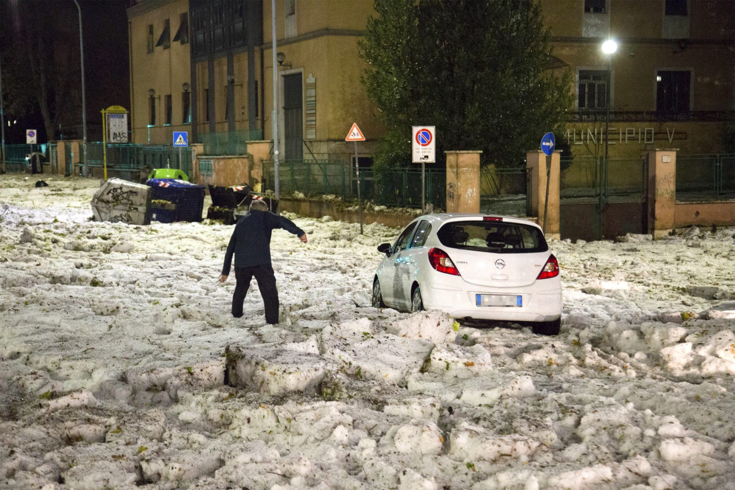 In this photo made available Monday Oct. 22, 2018 a man tries to reach a car blocked by ice after a hailstorm hit Rome in the evening of Sunday Oct. 21, 2018. The storm created flowing rivers of ice blocks and trapped dozen of drivers in their cars in the Eastern neighborhoods of Rome. (Massimo Percossi/ANSA via AP)