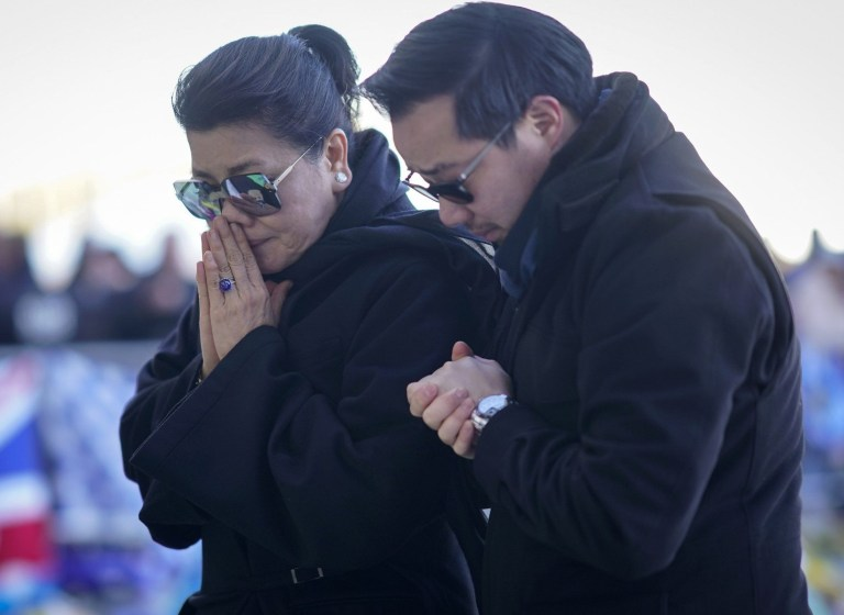 LEICESTER, ENGLAND - OCTOBER 29: Aiyawatt Srivaddhanaprabha (R) and Aimon Srivaddhanaprabha (L), the son and wife of Leicester City owner Vichai Srivaddhanaprabha who died in a helicopter crash at the club's stadium, pray after laying wreathes among the sea of tributes to the victims of the crash at Leicester City Football Club's King Power Stadium, on October 28, 2018 in Leicester, England. The owner of Leicester City Football Club, Vichai Srivaddhanaprabha, was among the five people who died in the helicopter crash on Saturday evening after the club's game against West Ham. (Photo by Christopher Furlong/Getty Images)