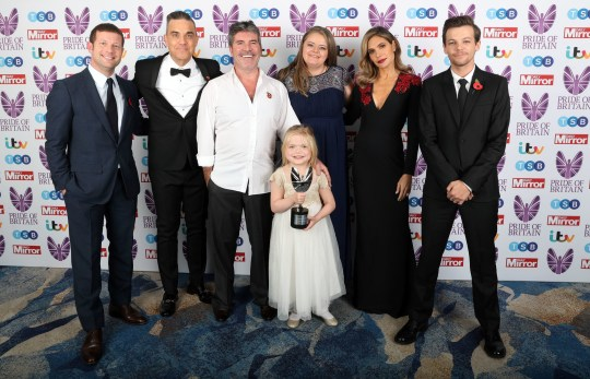 Ella Chadwick (front) wins Child of Courage award from (left to right) Dermot O'Leary, Robbie Williams Simon Cowell, Karen Chadwick (Ella's mum), Ayda Field and Louis Tomlinson during the Pride Of Britain Awards 2018, in partnership with TSB, honouring the nation's unsung heroes and recognising the amazing achievements of ordinary people, held at the Grosvenor House Hotel, London. PRESS ASSOCIATION PHOTO. Picture date: Monday October 29, 2018. See PA story SHOWBIZ Pride. Photo credit should read: Steve Parsons/PA Wire