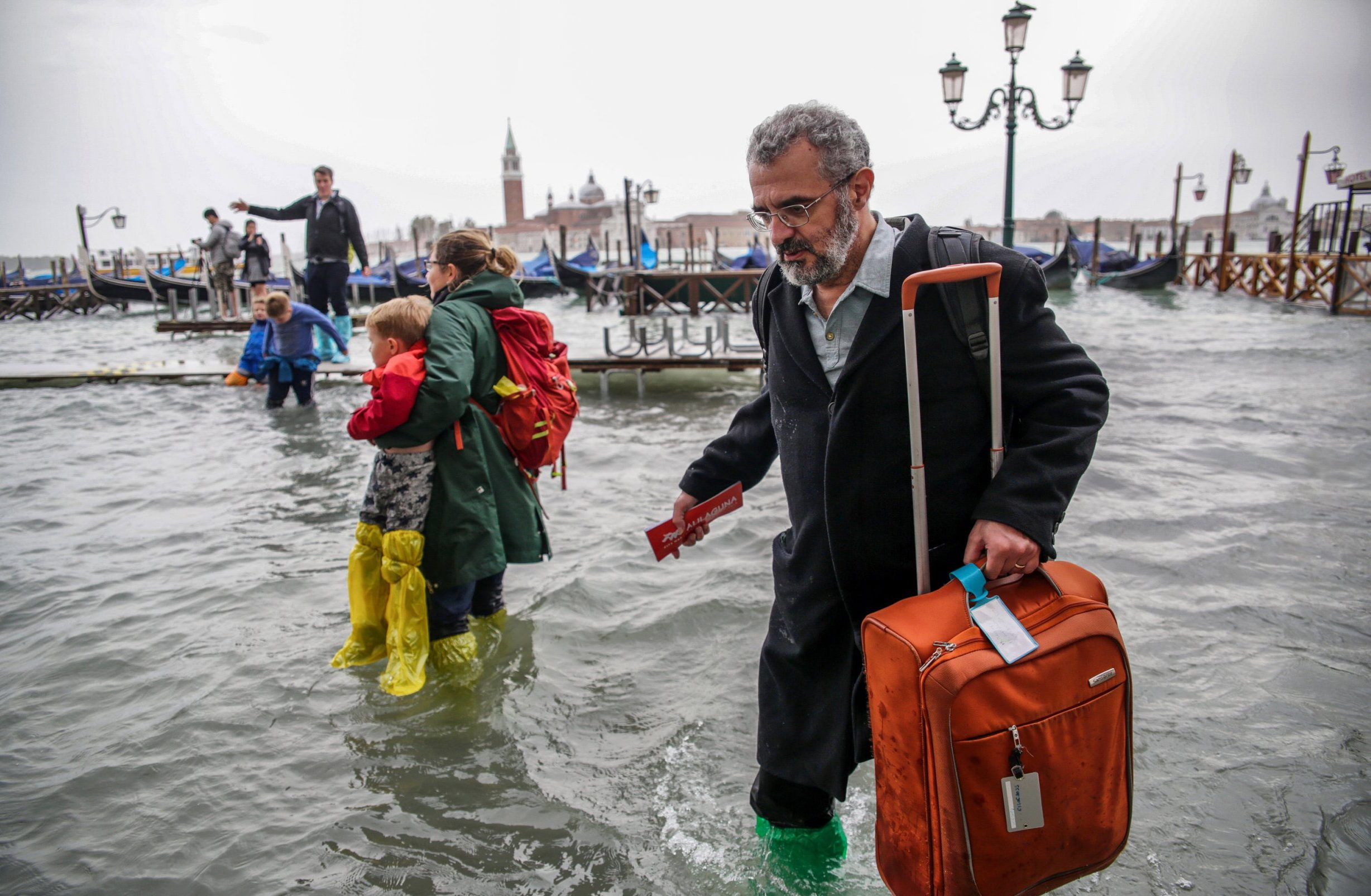 Mandatory Credit: Photo by Mirco Toniolo/Ropi/REX (9948537b) Tourists walk in the high water near St Mark's Square Flooding in Venice, Italy - 29 Oct 2018