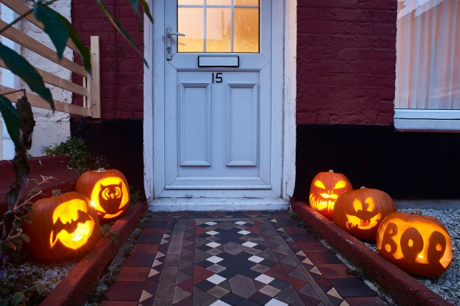 Carved pumpkins lining a path up to a door of a house on halloween. The pumpkins have been carved and are lit.