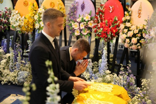 In this photo issued by King Power, player Jamie Vardy, right, with other players and officials of English Premier League club Leicester City participate in the funeral rituals of Vichai Srivaddhanaprabha in Bangkok, Thailand, Sunday, Nov. 4, 2018. An elaborate funeral began Saturday for Thai billionaire and Leicester City owner Vichai Srivaddhanaprabha, who died last week when his helicopter crashed in a parking lot next to the English Premier League club's stadium. (King Power via AP)