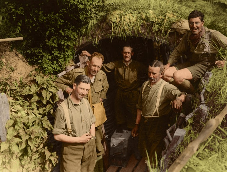 British soldiers in a German trench, Messines, Belgium, 1917. Three officers stand outside the mouth of the trench whilst one sits on top of it and one stands inside it. They all appear happy or relaxed, presumably as they have just captured a German trench and all the supplies in it. THE GRIM reality of World War One has been remembered in a series of 100 colourised images to commemorate the 100th anniversary of the end of the Great War. The incredible images show Royal Garrison Artillery gunners pushing a light railway truck filled with shells in 1917, a British soldier helping a wounded German prisoner walk along a railway track in 1916 and British officers standing outside the mouth of a German trench in Messines, Belgium, 1917 after capturing it. Other striking pictures show King George V sitting next to an army commander, Thiepval, France on the site where Thiepval Chateau once stood, a soldier receiving a haircut from an Alpine barber on the Albanian front and a group of Irish soldiers recuperating with nurses c1917. The original black and white photographs were painstakingly colourised by Tom Marshall of PhotograFix to mark the 100th anniversary of World War One ending. Tom Marshall (PhotograFix) / mediadrumimages.com