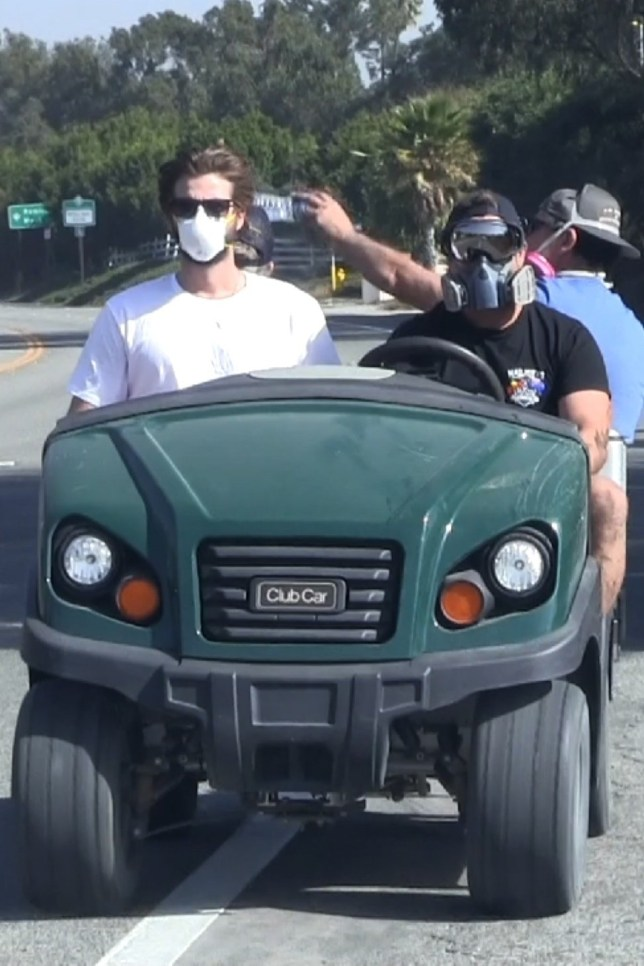 Liam Hemsworth wears a respirator at site of his burned down