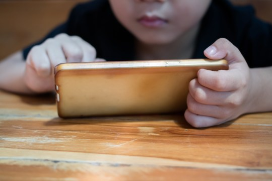 A cute Asian boy is using a smartphone.Concepcion on the problems of children with smartphones.; Shutterstock ID 740508259; Purchase Order: -