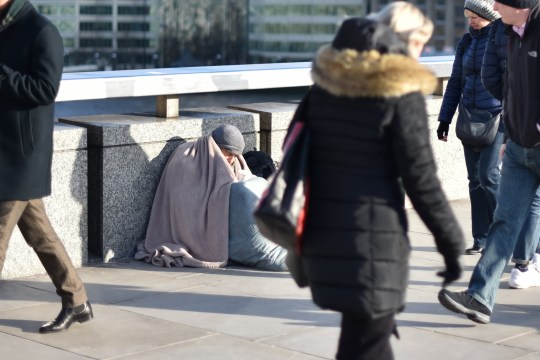 LONDON, ENGLAND - MARCH 19: A homeless person wrapped in a blanket sits holding a cup on London Bridge as people walk past at the start of rush hour on March 19, 2018 in London, England. (Photo by John Keeble/Getty Images)