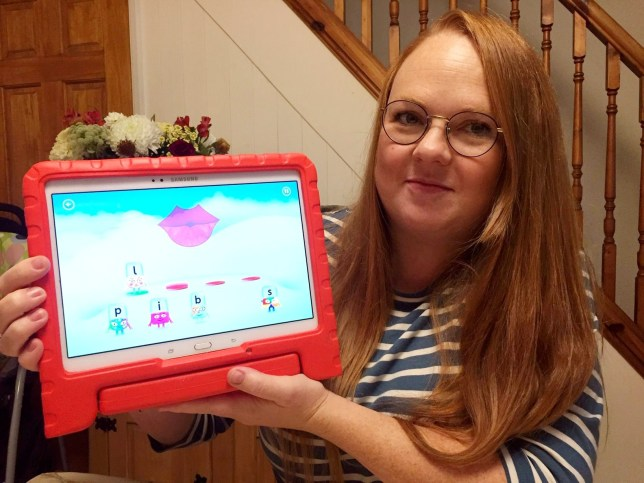 """Emma Shepherd with the children's game which makes an unfortunate sound. See SWNS story SWBRorgasm; A mum says a game on her two-year-old son's CBeebies Playtime app sounds like a woman - having an ORGASM. Emma Shepherd, 37, said son Oscar's Alphablocks features a pair of pink lips which make a sexual 'moaning' noise. On the app the child is tasked with writing a word and has five scrabble-style tiles to select from. When they click on a letter, the lips make its phonic sound to help teach children the alphabet - but the 'l' appears to imitate more sexual vocals. Mum-of-two Emma, from Taunton, Somerset, says it's like it has been """"hacked by perverts""""."""