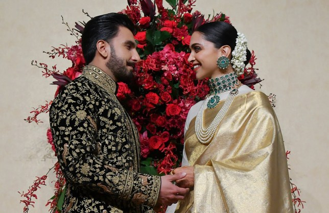Indian Bollywood actors Ranveer Singh (L) and Deepika Padukone pose for photographers during their wedding reception held at the Leela Palace in Bangalore on November 21, 2018. - The couple tied the knot in a private family affair held in Italy on November 14 and 15. (Photo by MANJUNATH KIRAN / AFP) (Photo credit should read MANJUNATH KIRAN/AFP/Getty Images)