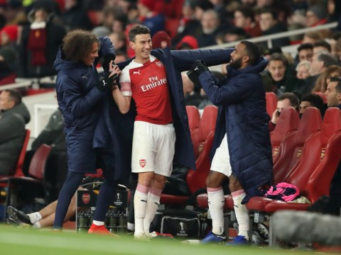 Arsenal captain Laurent Koscielny offers advice to injured teammate Rob Holding