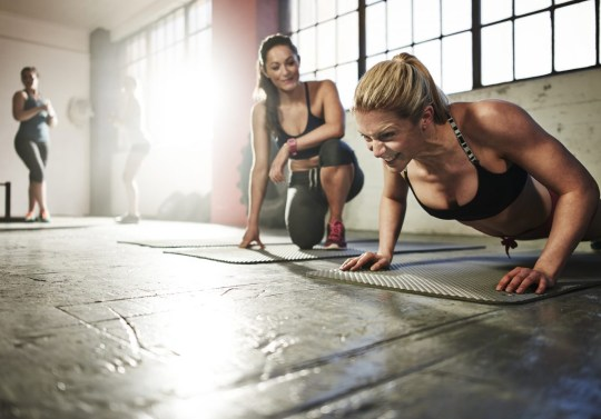 A young woman struggles to do a press-up in the gym