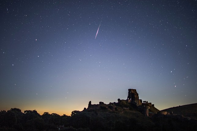 A Perseid meteor flashes across the night sky above Corfe Castle (Photo by Dan Kitwood/Getty Images)