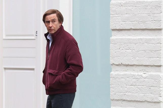 Alan Partridge outside a house