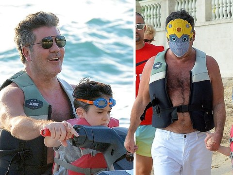 Simon Cowell plays the superhero with son Eric on the beach with Transformer masks