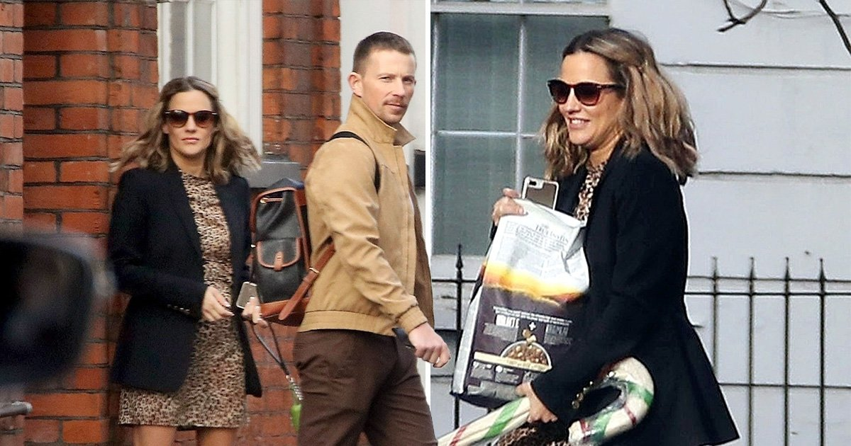 Caroline Flack looks pleased as punch as she leaves house with mystery man