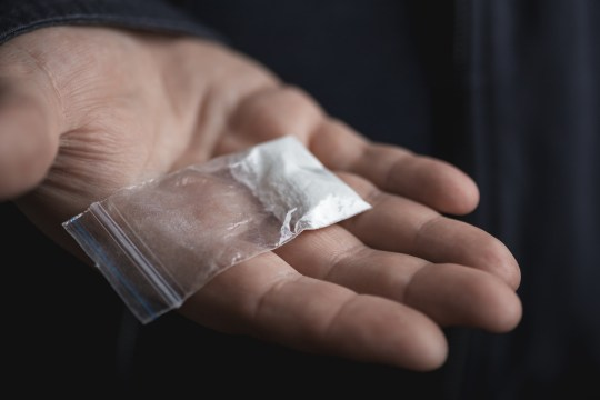 Mans hand holding on palm plastic packet with cocaine powder or another drugs. Drug dealer proposes to try narcotic concept, selective focus