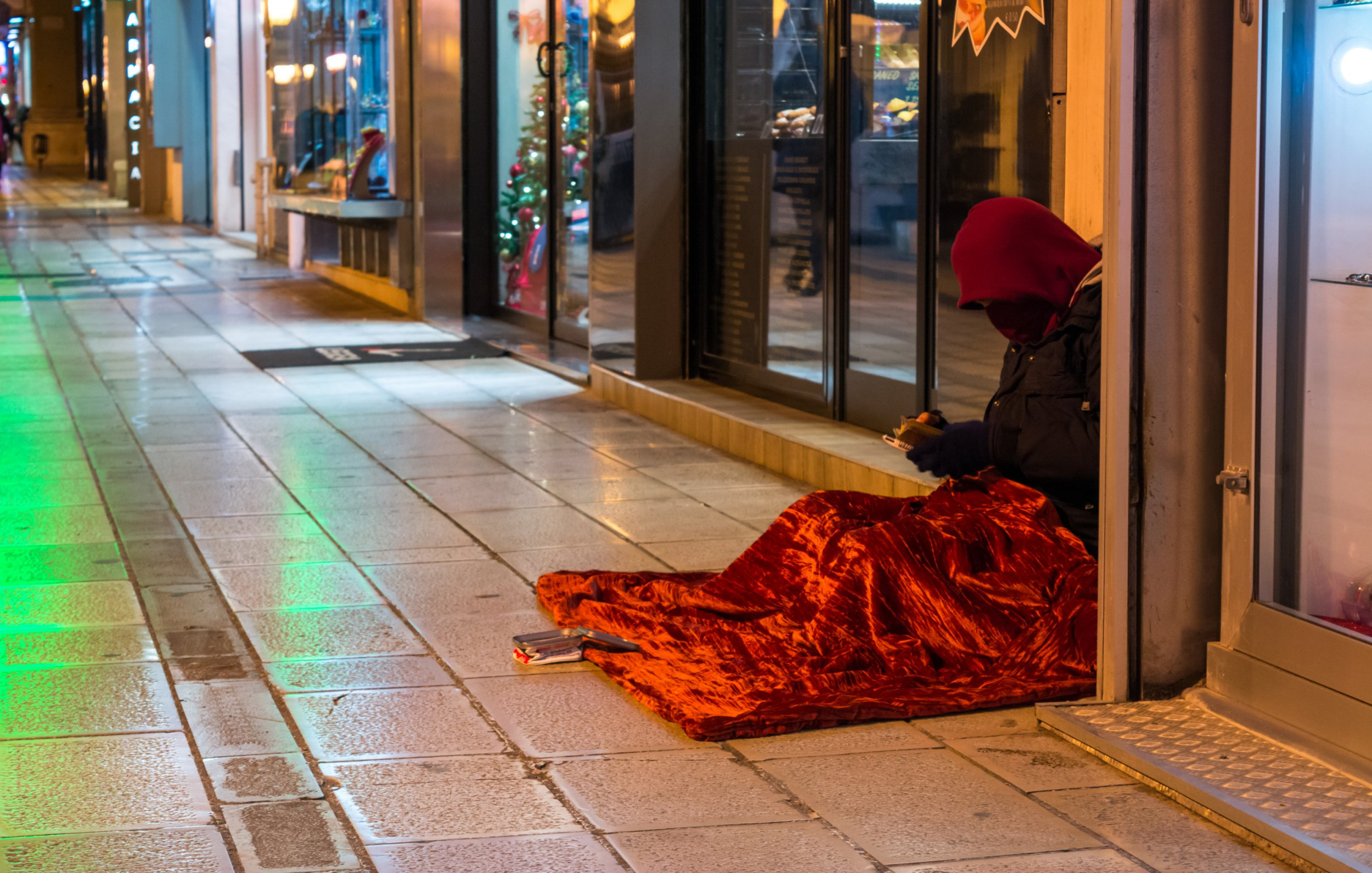 Hooded Clochard In A Street Near A Window Of A Shop During A Cold Day In The Christmas Period In Italy; Shutterstock ID 778924792; Purchase Order: -