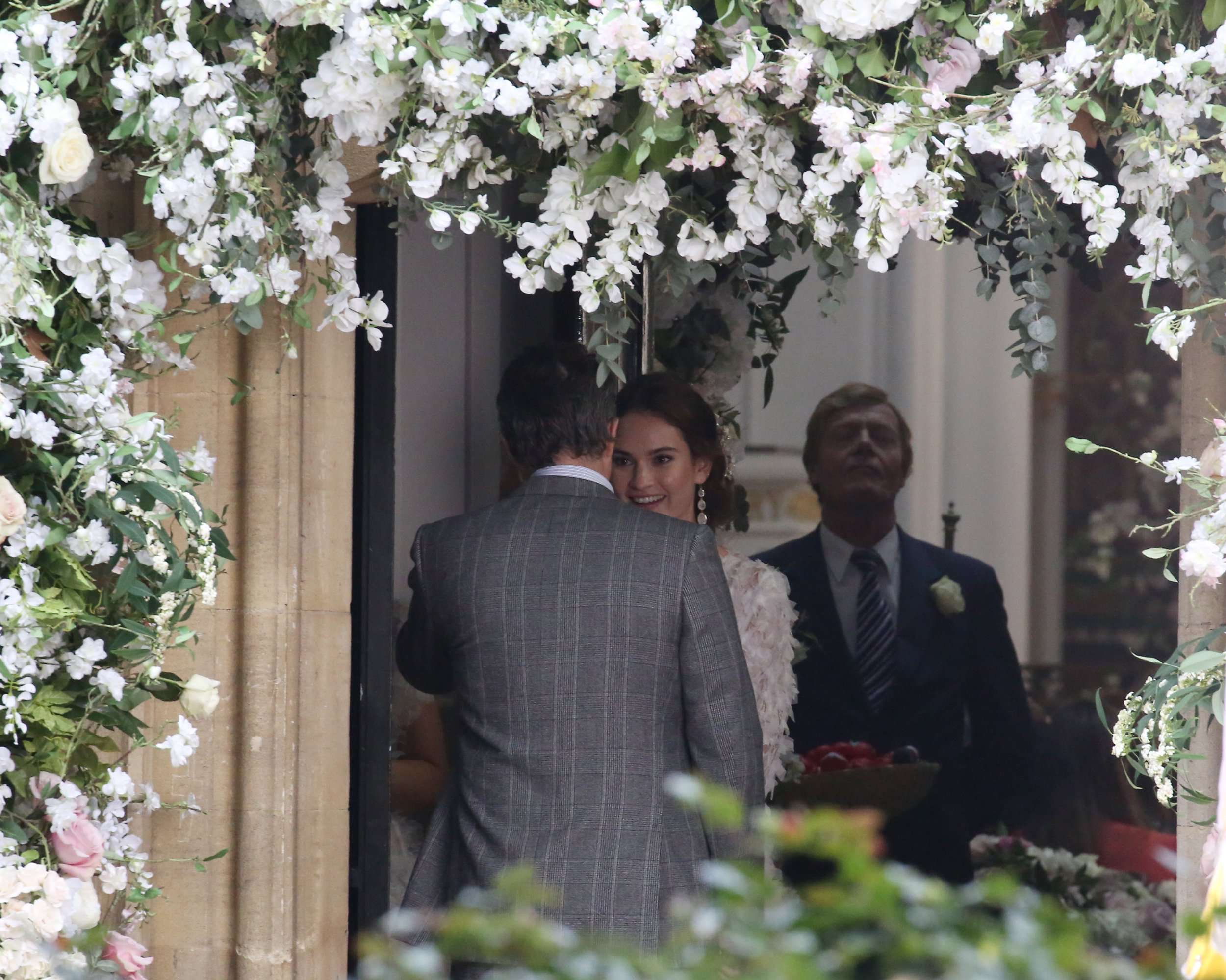 LONDON, ENGLAND - DECEMBER 14: Hugh Grant and Lily James seen filming 'Four Weddings and a Funeral' at a church in North London for Comic Relief, titled 'One Red Nose Day and a Wedding' on December 14, 2018 in London, England. (Photo by Neil Mockford/GC Images)