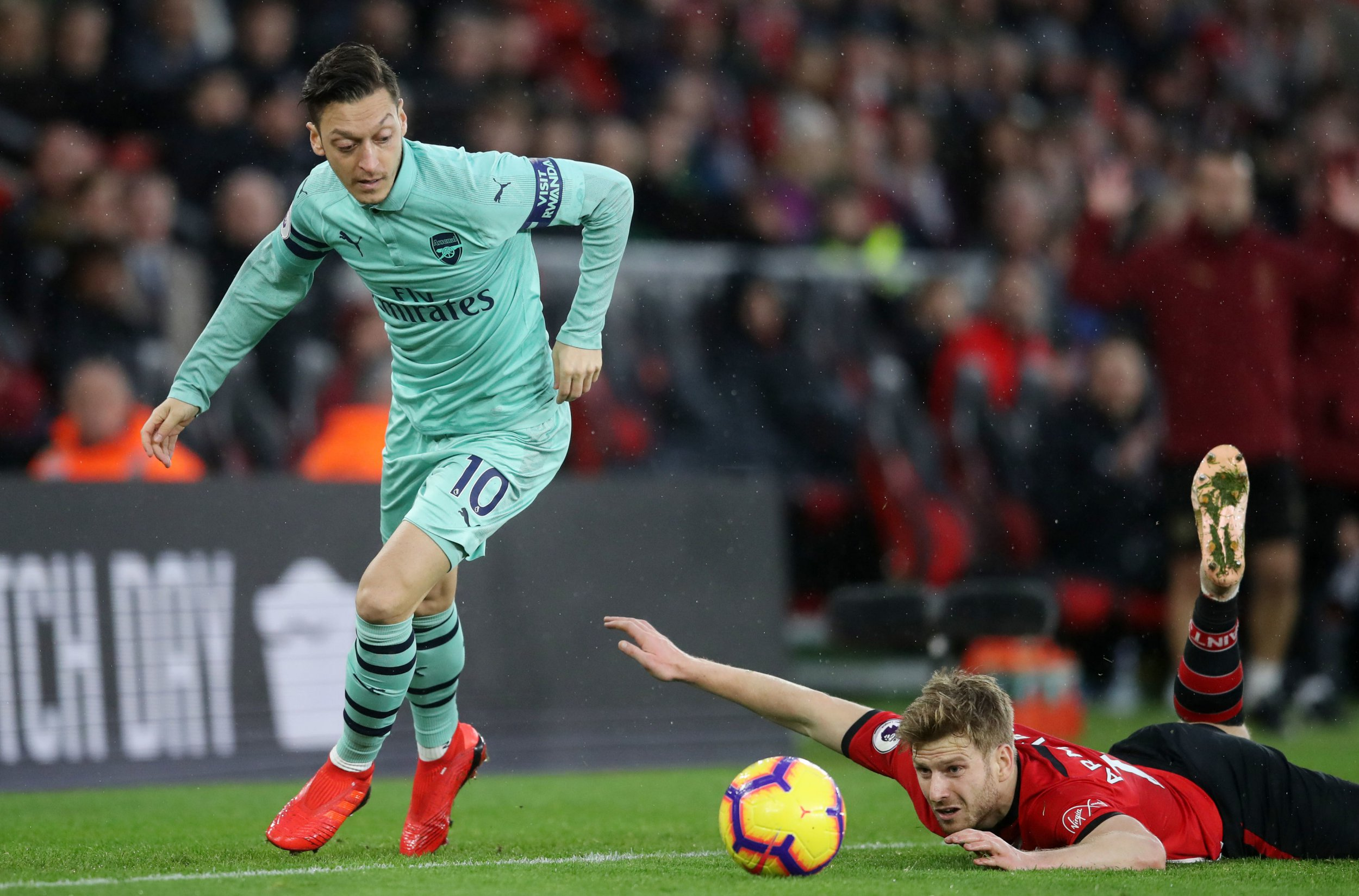 """Arsenal's Mesut Ozil jumps over a challenge from Southampton's Stuart Armstrong during the Premier League match at St Mary's Stadium, Southampton. PRESS ASSOCIATION Photo. Picture date: Sunday December 16, 2018. See PA story SOCCER Southampton. Photo credit should read: Adam Davy/PA Wire. RESTRICTIONS: EDITORIAL USE ONLY No use with unauthorised audio, video, data, fixture lists, club/league logos or """"live"""" services. Online in-match use limited to 120 images, no video emulation. No use in betting, games or single club/league/player publications"""