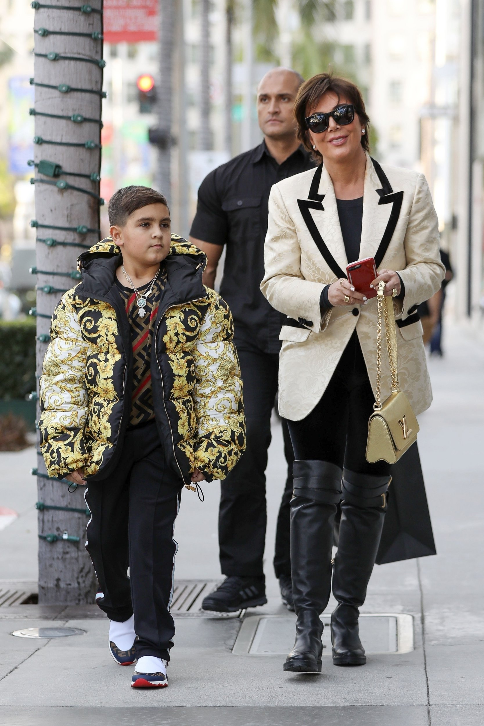 Beverly Hills, CA - Momager Kris Jenner gets her grandson Mason Disick an expensive looking Versace puffer jacket as they both go Christmas shopping in Beverly Hills with a bodyguard. Pictured: Kris Jenner, Mason Dash Disick BACKGRID USA 18 DECEMBER 2018 BYLINE MUST READ: Clint Brewer / BACKGRID USA: +1 310 798 9111 / usasales@backgrid.com UK: +44 208 344 2007 / uksales@backgrid.com *UK Clients - Pictures Containing Children Please Pixelate Face Prior To Publication*