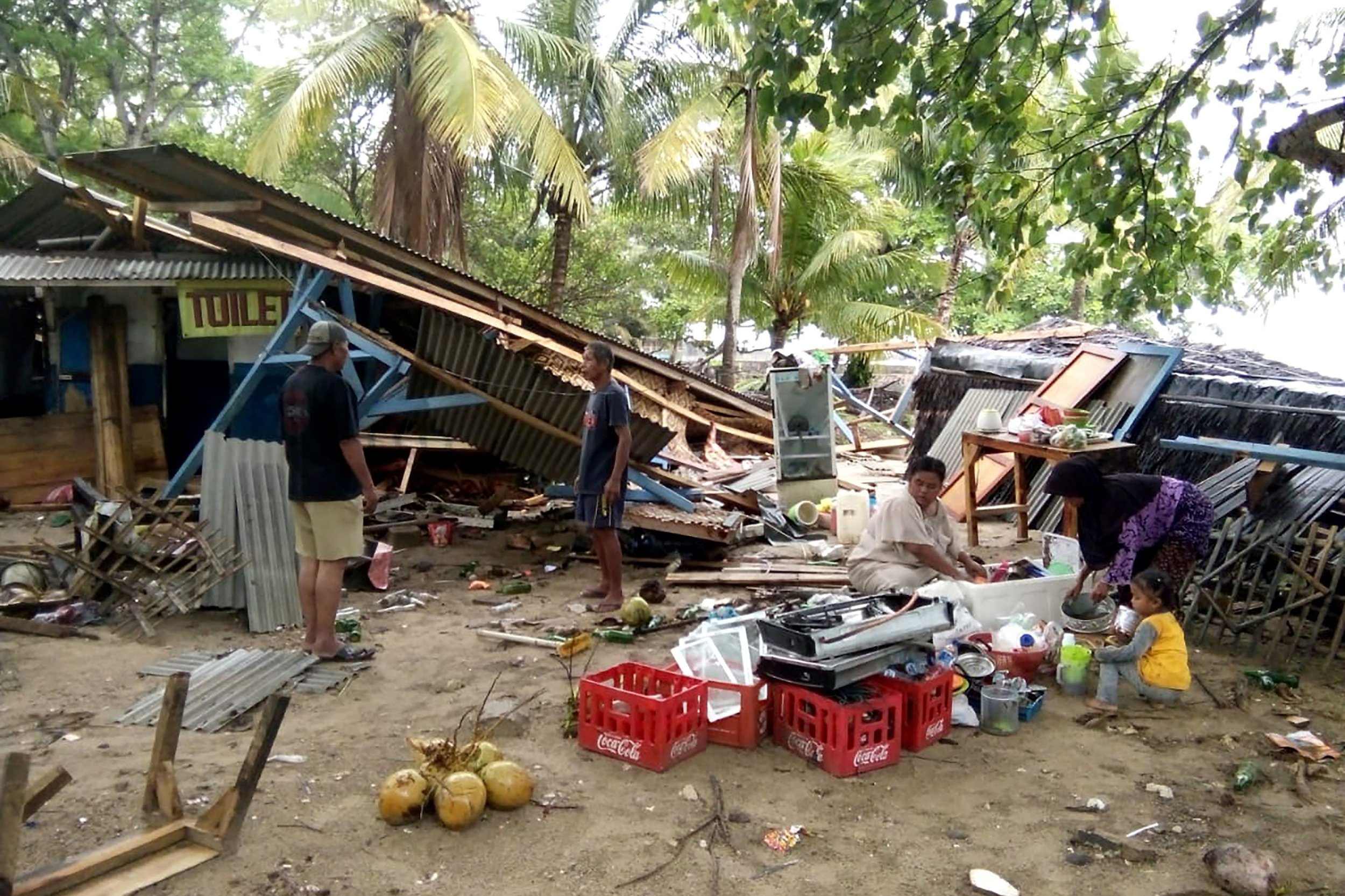 "People gather salvageable items from damaged buildings on Carita beach on December 23, 2018, after the area was hit by a tsunami that may have been caused by the Anak Krakatoa volcano. - At least 43 people have been killed and nearly 600 injured in a tsunami in Indonesia that may have been caused by a volcano known as the ""child"" of the legendary Krakatoa, officials said on December 23. (Photo by Semi / AFP)SEMI/AFP/Getty Images"